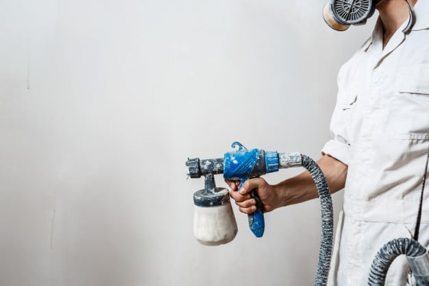 worker-painting-wall-with-spray-gun-white-color_176420-4735